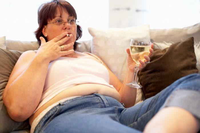полная женщина курит и употребляет алкоголь на диване
