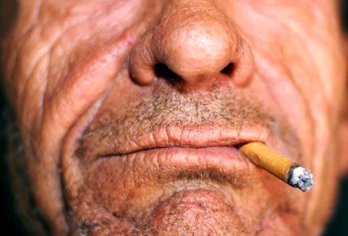 пожилой мужчина курит сигарету