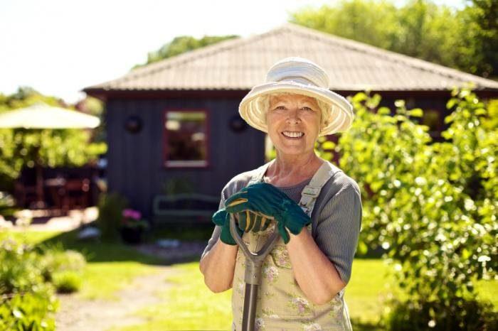 пожилая женщина с лопатой улыбается