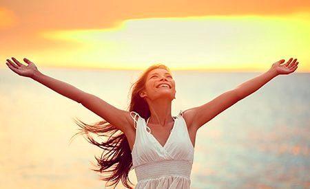 девушка тянет руки к солнцу