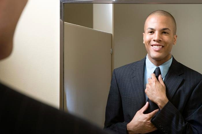 мужчина поправляет галстук перед зеркалом