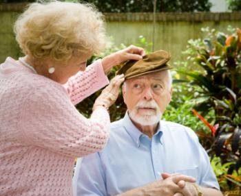 болезнь альцгеймера. Пожилая женщина поправляет кепку у пожилого человека