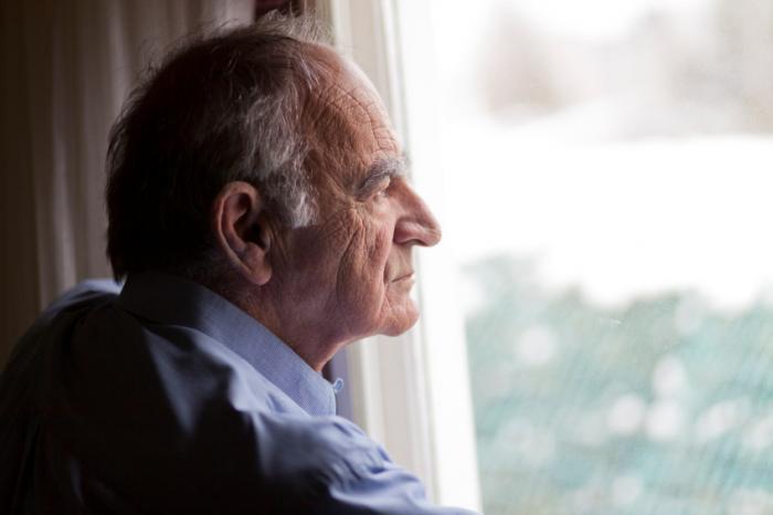 пожилой мужчина скучает у окна