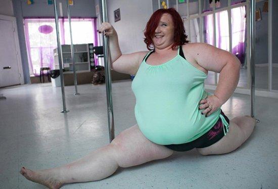 толстая девушка сидит на шпагате в зале