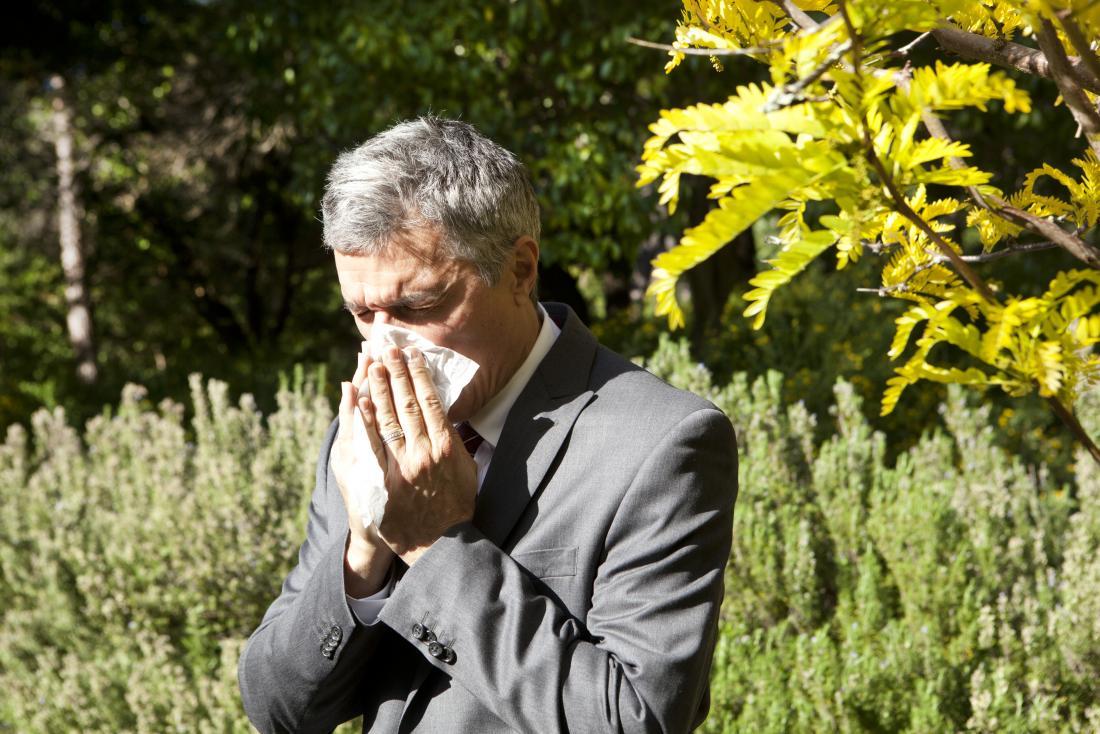 мужчина закрывает нос платком
